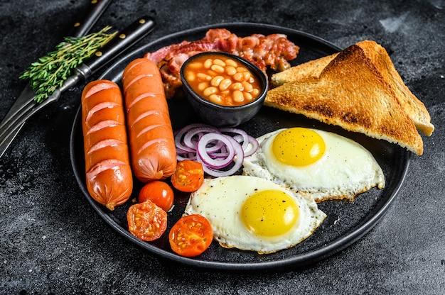 Prima colazione inglese con uova fritte, salsicce, pancetta, fagioli e toast in un piatto