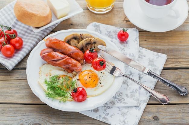 Prima colazione inglese con uova fritte, salsicce, funghi, pomodori grigliati e succo d'arancia fresco sul tavolo in legno rustico. concetto di sana colazione.