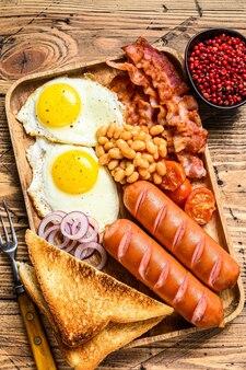 Prima colazione inglese in un vassoio di legno con uova fritte, salsicce, pancetta, fagioli e toast