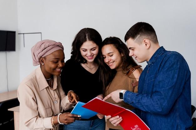Studio in classe di inglese con studenti di diversi paesi: polonia, germania, usa. lavoro di squadra. lavorare in studenti multietnici. l'insegnante studia le lingue straniere insieme in classe. studiare con il laptop.