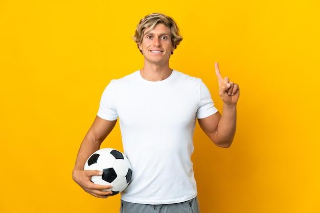 Giocatore di football inglese su giallo isolato che indica su una grande idea