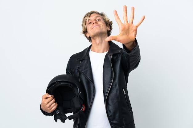 Uomo inglese che tiene un casco del motociclo che conta cinque con le dita