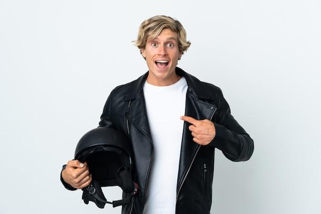 Uomo inglese che tiene un casco da motociclista con espressione facciale a sorpresa