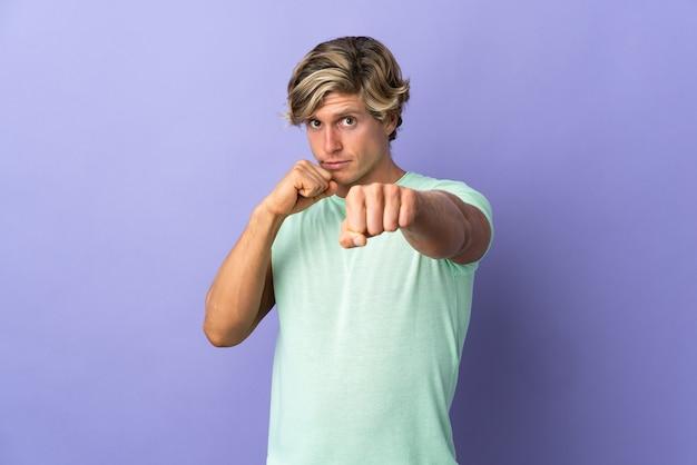 Uomo inglese sopra la parete viola isolata con il gesto di combattimento