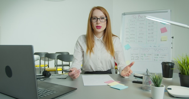 Insegnante di inglese insegnamento virtuale guarda la webcam dare lezione a distanza.