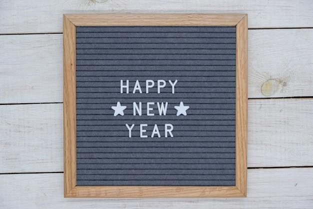 Testo inglese felice anno nuovo e due stelle su una tavola di feltro in una cornice di legno. lettere bianche su sfondo grigio.