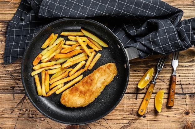 Piatto tradizionale inglese di pesce e patatine fritte con patatine fritte in padella. fondo in legno. vista dall'alto.
