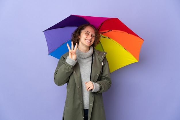 Donna inglese che tiene un ombrello isolato sulla parete viola felice e contando tre con le dita