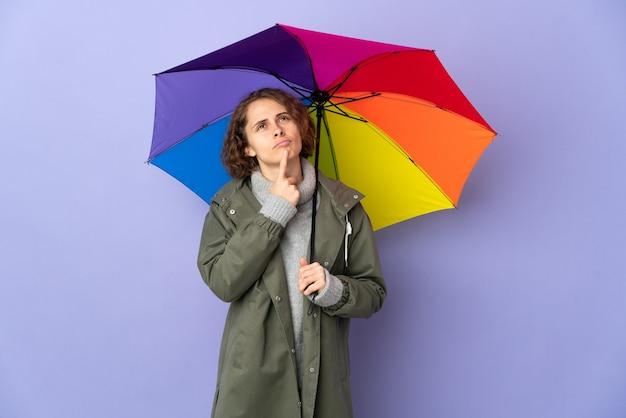 Donna inglese che tiene un ombrello isolato sulla parete viola che ha dubbi mentre osserva in su