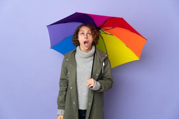 Donna inglese che tiene un ombrello isolato sulla parete viola che osserva in su e con l'espressione sorpresa