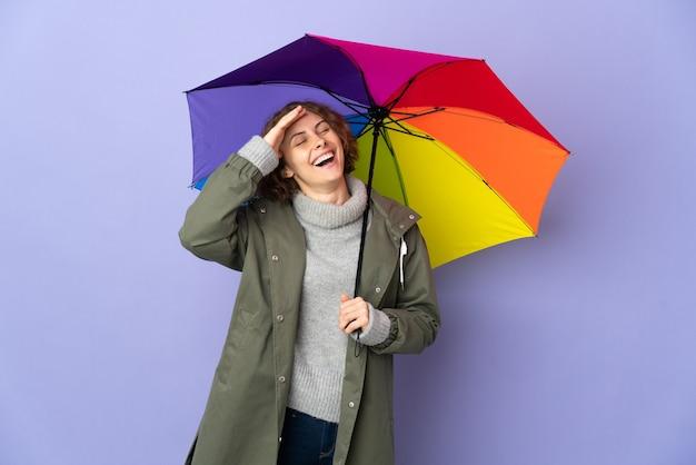 Donna inglese che tiene un ombrello isolato sulla parete viola che sorride molto