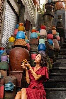 Goditi l'attimo. carina ragazza bruna che mantiene il sorriso sul viso guardando un piccolo vaso giallo