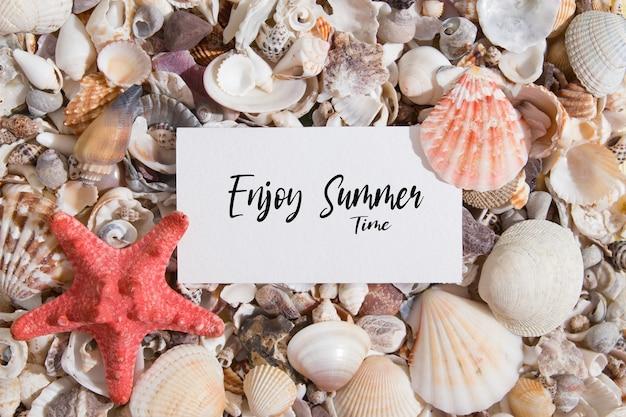Goditi le scritte estive su un pezzo di carta su conchiglie e stelle marine. testo di motivazione estiva piatta