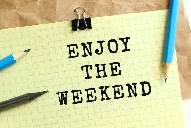 Goditi la scritta weekend su un foglio di carta giallo su carta kraft stropicciata. matite e graffetta.