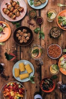 Buona cena! vista dall'alto di cibo e bevande sul tavolo in legno rustico