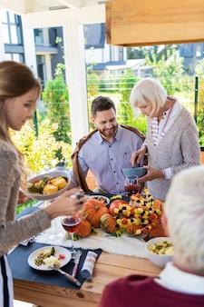 Buon appetito. attiva giovane donna tenendo la piastra nella mano sinistra mentre guarda la tavola festiva