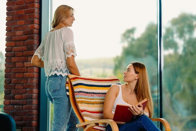 Goditi il tuo tempo in un'atmosfera accogliente con un libro, su una sedia a dondolo e chiacchierando con un buon amico. bell'interno con grandi finestre.