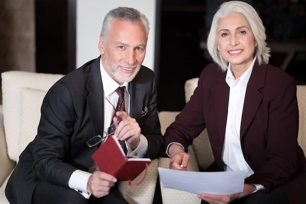 Piacevole processo di condivisione delle opinioni. felice uomo d'affari invecchiato allegro sorridente e seduto in ufficio vicino alla donna d'affari mentre si lavora con il suo collega e lo scambio di idee