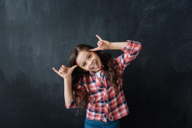 Piacevole fine settimana. bambino divertito divertente giocoso in piedi nella lavagna e suonare la scimmia mentre esprime gioia