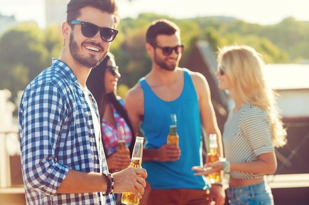 Gustare la birra con gli amici. felice giovane che tiene in mano una bottiglia di birra e guarda la telecamera mentre tre persone parlano tra loro in sottofondo