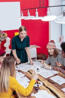 Godersi la lezione. studenti che si godono la lezione con un bravo insegnante di talento in una stanza spaziosa con pareti rosse