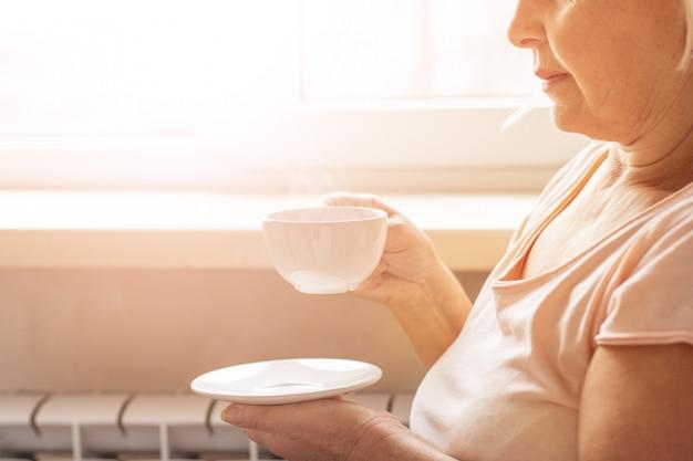 Godendo il tempo del caffè a casa. donna e caffè nelle mani