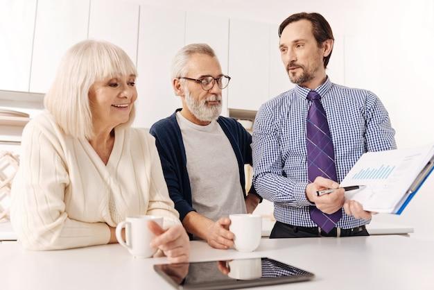 Mi piace consultare i miei clienti. allegro diligente agente immobiliare istruito incontro con coppia senior di clienti mentre presenta il progetto ed esprime gioia
