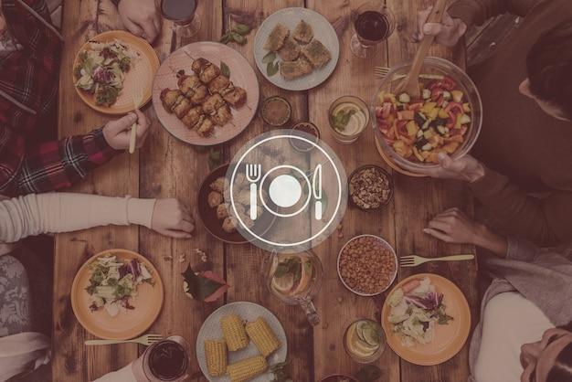 Godendo la cena insieme. vista dall'alto di quattro persone che cenano insieme seduti al tavolo di legno rustico