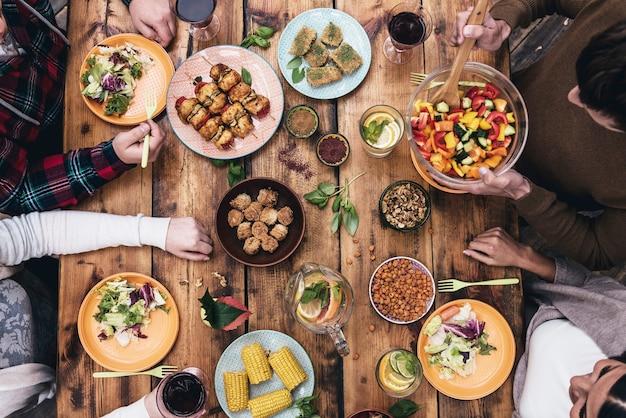 Godendo la cena insieme. vista dall'alto di quattro persone che cenano insieme