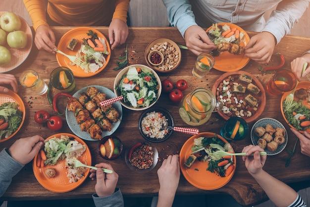 Godendo la cena con gli amici. vista dall'alto di un gruppo di persone che cenano insieme seduti al tavolo di legno rustico