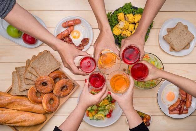 Godendo la cena con gli amici. vista dall'alto di un gruppo di persone che cenano insieme seduti al tavolo di legno
