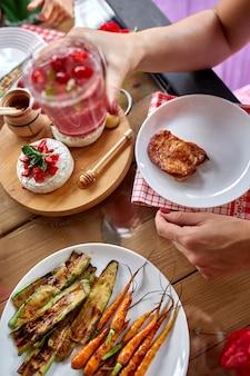 Godendo la cena donna mangia, beve limonata, tavolo da pranzo, varietà di antipasti che servono sul tavolo all'aperto della festa a casa.