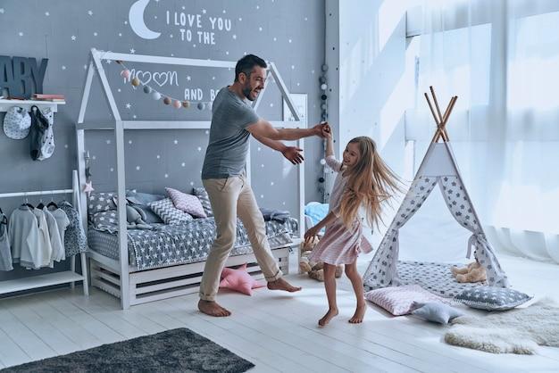 Godendo ogni minuto insieme. padre e figlia si tengono per mano e sorridono