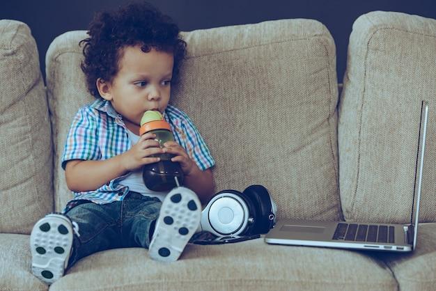 Godendo di catoon preferiti. vista frontale del piccolo bambino africano che beve dal biberon e guarda il suo laptop mentre è seduto sul divano di casa