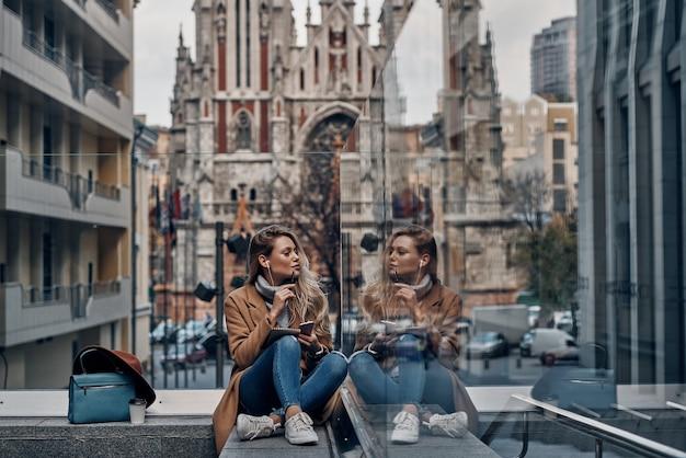 Godendo della musica preferita. attraente giovane donna che ascolta musica usando il suo smartphone e guardando il suo riflesso nella teca di vetro mentre trascorre del tempo spensierato in città