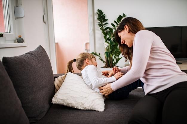 Godendo il tempo divertente. madre che solleticava sua figlia a casa.