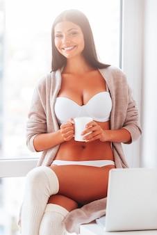 Godendo buongiorno. bella giovane donna in lingerie e maglione che tiene una tazza di caffè e sorride mentre è seduta vicino alla finestra a
