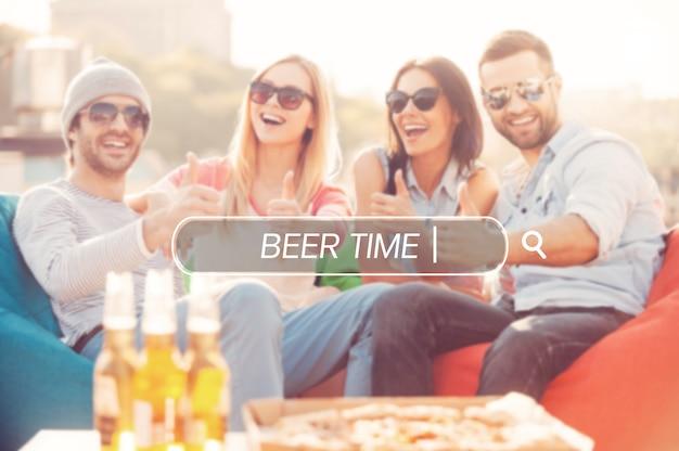 Godendo del buon tempo. quattro giovani allegri che mostrano i pollici in su e sorridono mentre sono seduti su sacchi di fagioli sulla terrazza all'aperto con pizza e birra in primo piano