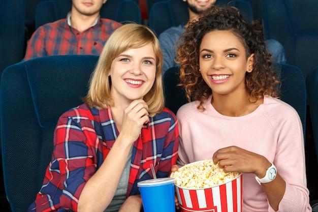 Godendo di una commedia fantastica. due belle amiche che ridono allegramente guardando un film nel cinema locale