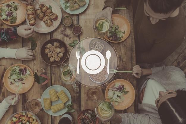 Godendo un'ottima cena. vista dall'alto di quattro persone che cenano insieme seduti al tavolo di legno rustico