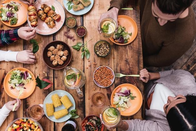 Godendo un'ottima cena. vista dall'alto di quattro persone che cenano insieme