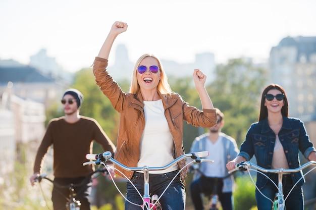Divertirsi con gli amici. bella giovane donna sorridente che va in bicicletta e tiene le braccia alzate mentre i suoi amici cavalcano sullo sfondo