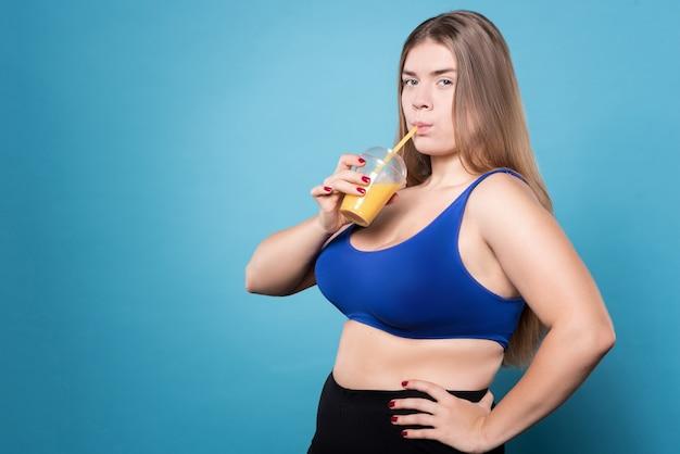 Godersi una dieta sana. donna in sovrappeso che beve succo d'arancia e che tiene le braccia sui fianchi.