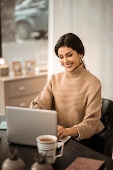 Godendo il suo lavoro. bella signora positiva in maglione beige seduto alla scrivania con una tazza di tè e digitando sulla tastiera del computer portatile