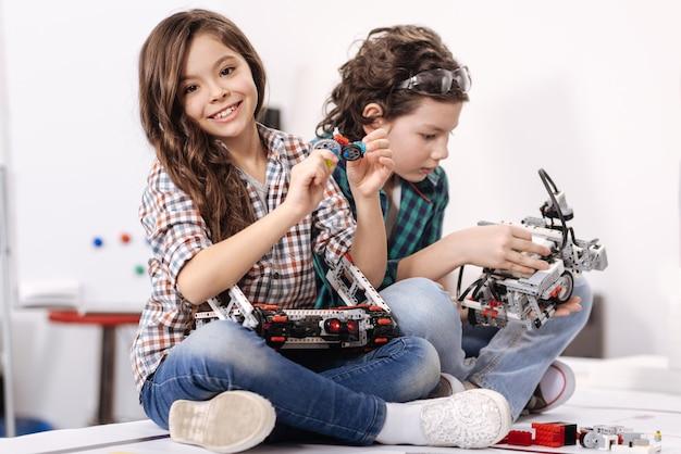 Divertirsi con i giochi interattivi. bambini felici intelligenti e ottimisti seduti a casa e utilizzando gadget e dispositivi mentre esprimono felicità