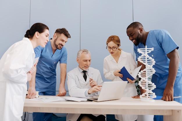 Godersi insieme un argomento interessante. abili giovani stagisti diligenti che studiano e si godono la lezione nella facoltà di medicina mentre conversano con un professore anziano e usano insieme il laptop