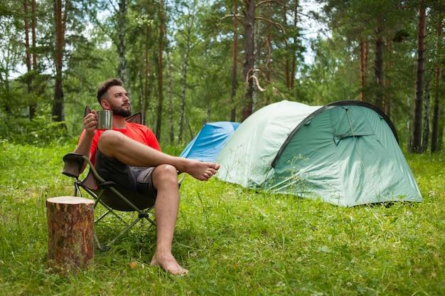 Godersi la vita. il giovane in natura beve il tè, in un campeggio. relax, vacanze, concetto di lifestyle