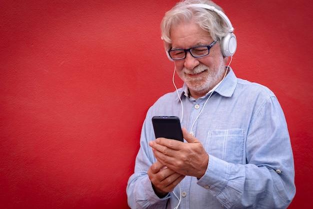 Godersi la musica. uomo anziano dai capelli bianchi con le cuffie in piedi su sfondo rosso guardando il suo smartphone