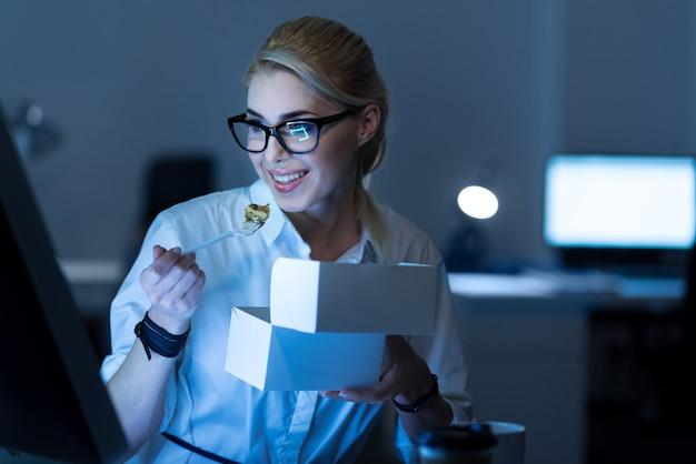 Godendo il mio tempo libero. affascinante piacevole segretaria felice seduta in ufficio e mangiare mentre esprime positività e guarda il computer