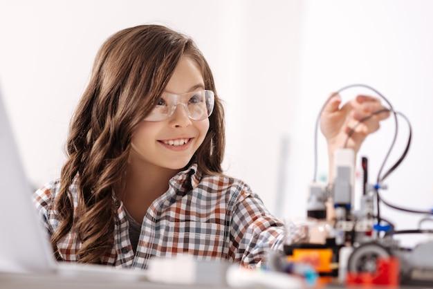 Godendo il mio hobby. sorridente bambino dotato intelligente seduto in classe di scienze e utilizzando dispositivi mentre studia ed esprime felicità